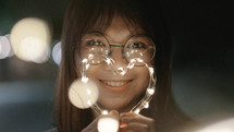 a young woman holding fairy lights in the shape of a heart