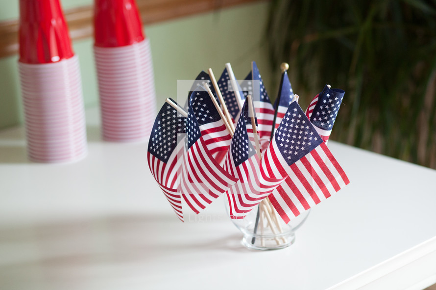 American flags in a vase and red cups