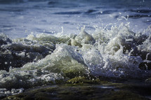 Wave washes over a rock bringing sea water washing onto a shore