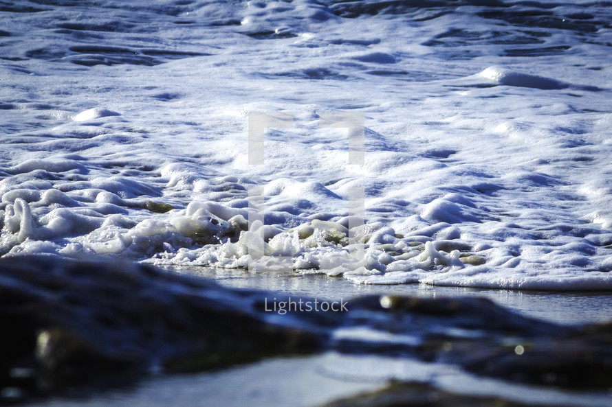 A wave gently flows to the beach with sea foam.