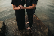 a couple holding hands standing in water