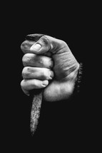 a hand grasping a nail spike