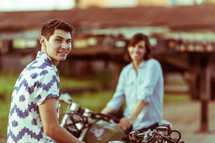 a couple sitting on motorcycles