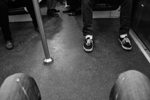 passengers feet on a subway train