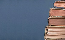 Stack of old books on a blue background