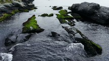 water flowing over rocks along a shore