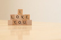 """ I love you"" spelled out in stacked scrabble tiles"