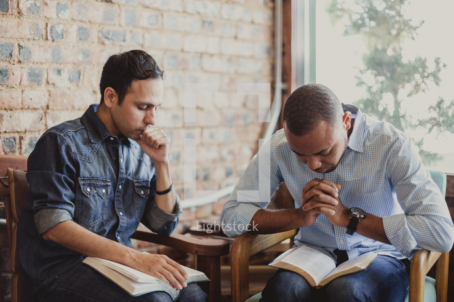 Latino man and African-American man reading Bibles