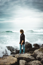 a man standing on rocky shore looking out at the crashing waves
