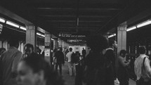 People walking through Brooklyn subway tunnel.