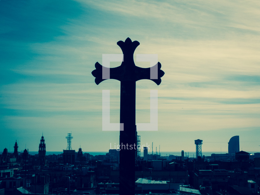 A gothic stone cross overlooking the sea-front city outlook, in cross-processed look.