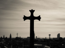 A gothic stone cross overlooking the sea-front city outlook, in black and white (b&w)