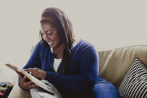 Woman sitting on the couch reading the Bible.