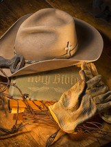Cowboy hat and leather work gloves on top of a Bible.