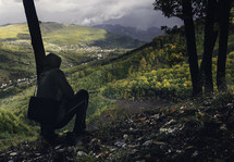 man squatting on a mountainside