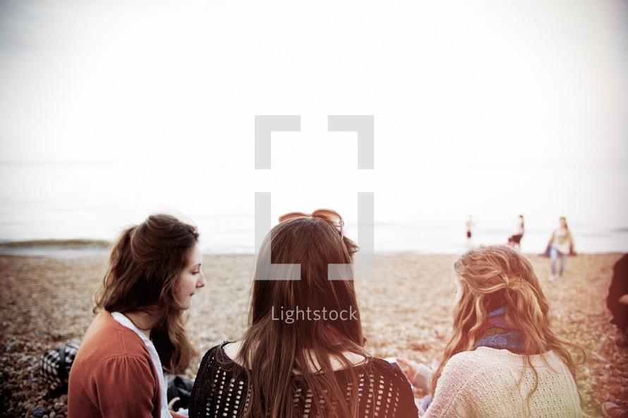 three friends sitting on a beach