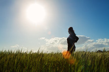girl in a field on tall grass under bright sun