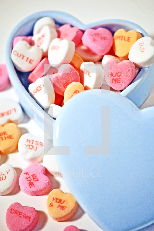 Candy hearts in a heart-shaped bowl.