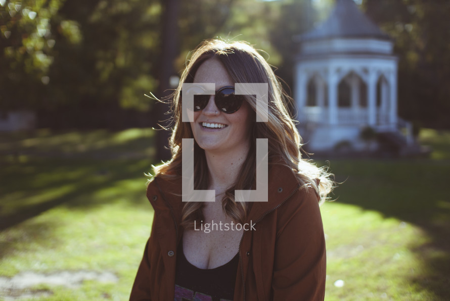 brunette woman standing outdoors wearing sunglasses