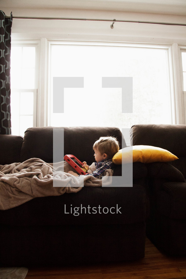 toddler lying on a couch using an iPad