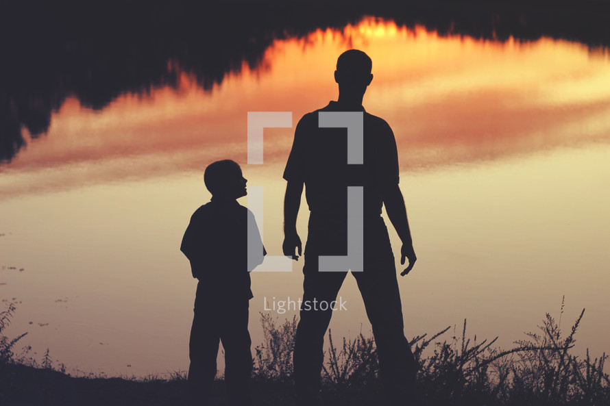 silhouette of a father and son standing by a lake