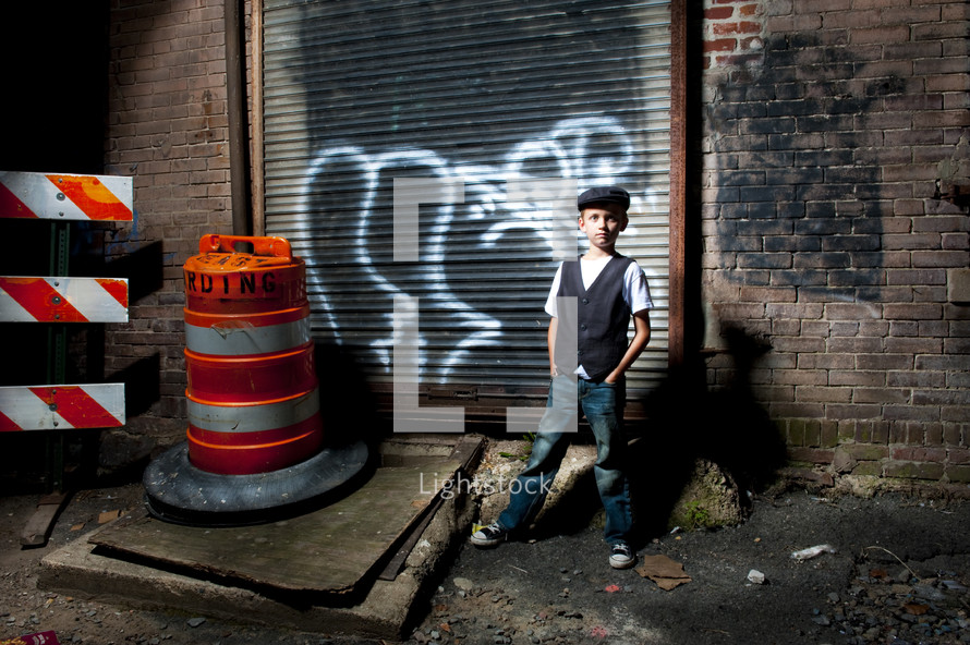boy standing in an alley next to a construction cone