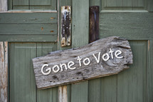 "Green wooden doors with a sign reading, ""Gone to Vote."""
