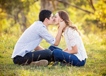 couple sitting and kissing outdoors
