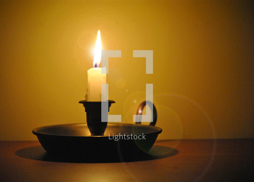 Lighted candle in candlestick.