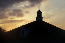 Steeple sunset - A building with a steeple and weather vein is silhouetted by a beautiful sunset just before dusk.