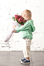 little boy holding a smelling a bouquet of flowers