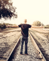 man with open arms on railroad tracks