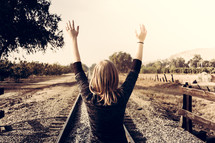 woman with arms raised standing on railroad tracks