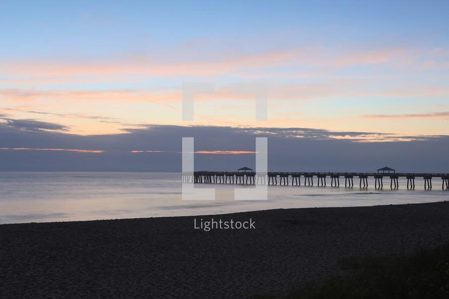 Long pier off beach in ocean at dusk.