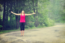 Woman walking outside in the rain with arms wide open.