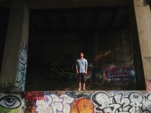 man standing on a graffiti covered wall