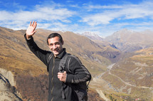 man waving on top of a mountain