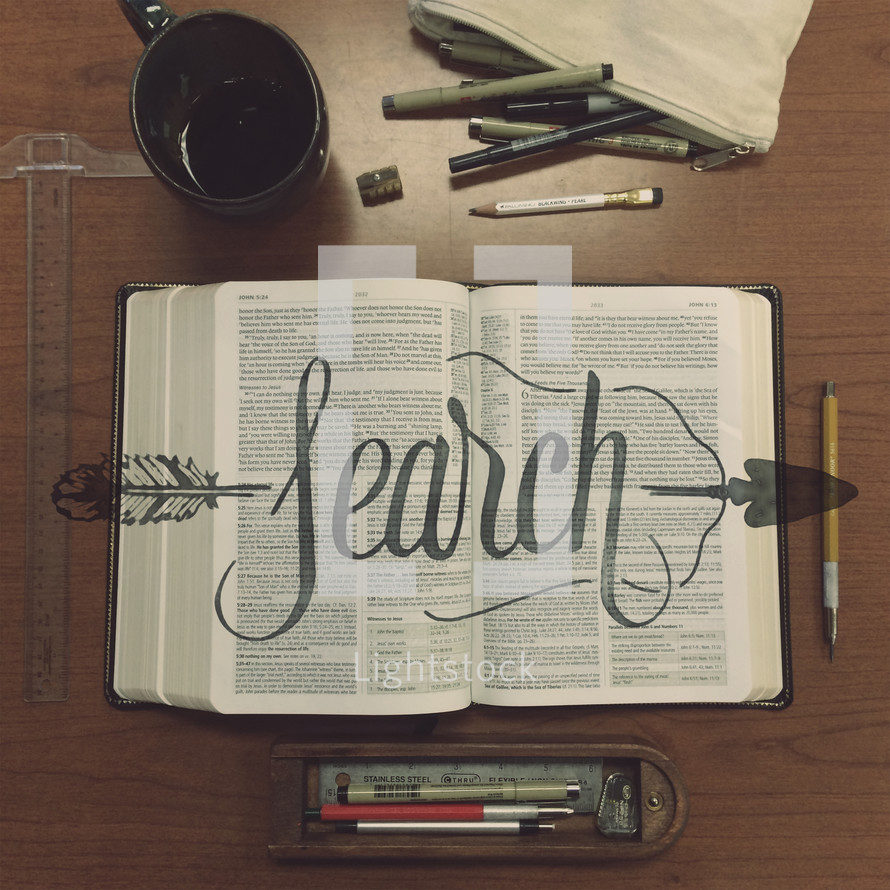 "The word ""search"" over an open Bible on a table with writing utensils."