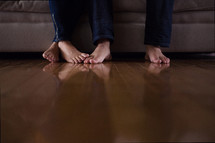 touching bare feet of a couple sitting on a couch watching tv.