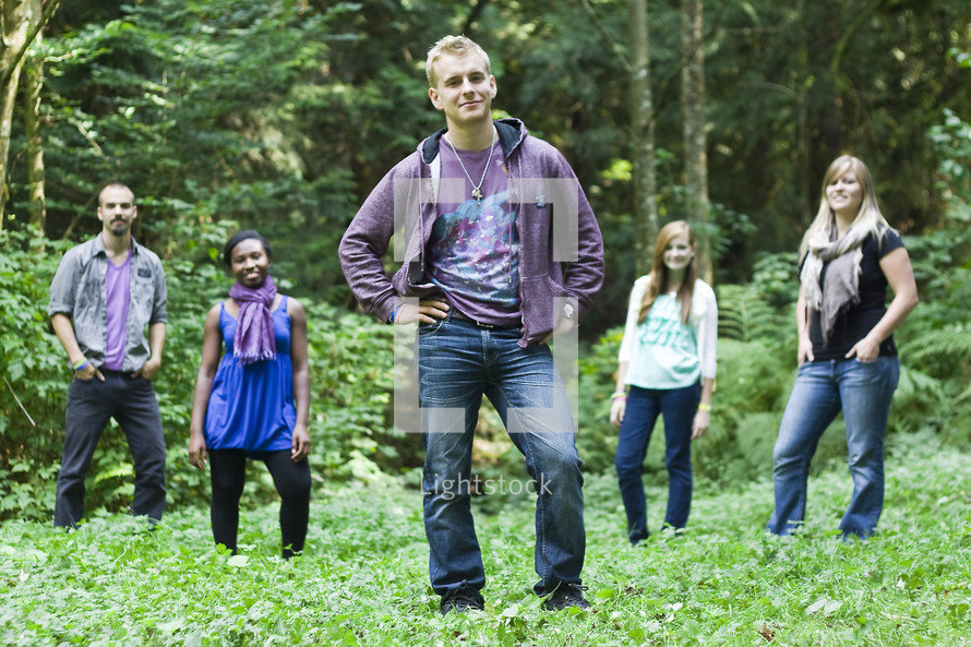Young adults (church interns) in a forest field with their hands on their hips and in pockets.