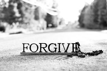 "Letters spelling ""forgive"" on the ground with a chain."
