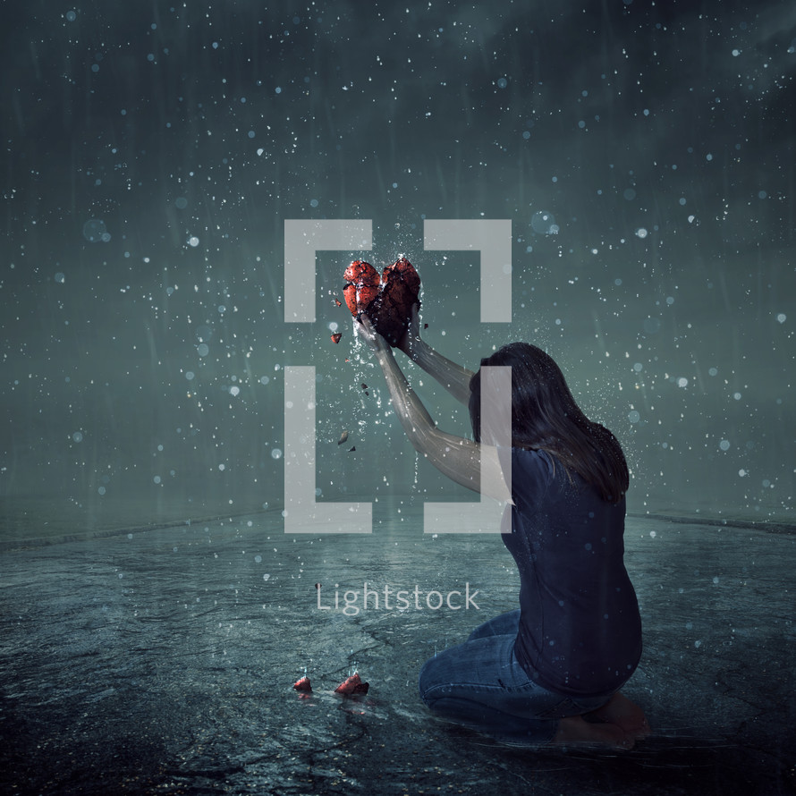 a woman on her knees holding a broken heart in the rain