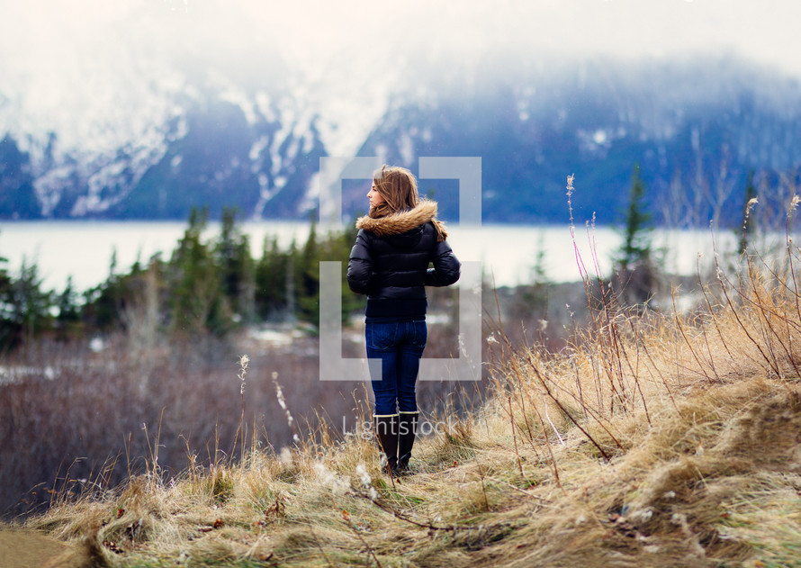 woman outdoors looking at a snowy mountain