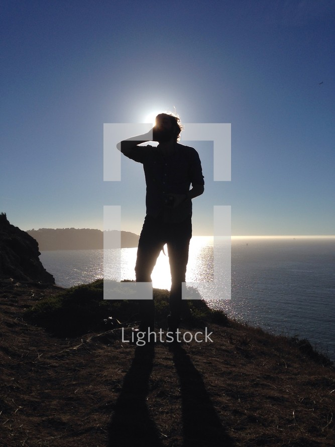 silhouette of a man standing at a lake shore under sunlight