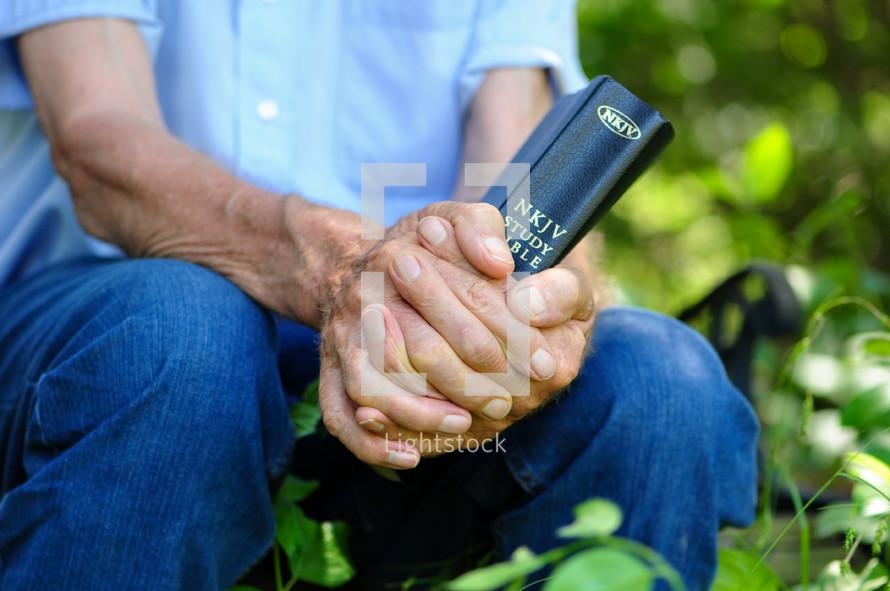 an elderly man clasping a Bible