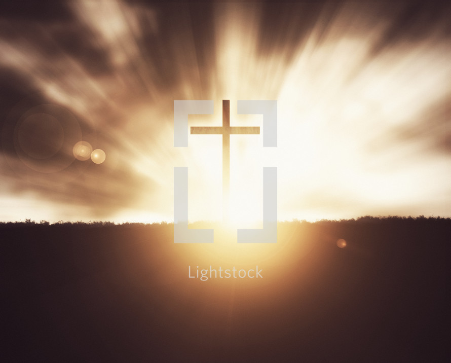 Silhouette of a cross on grassy field at sunset with glowing lights and lens flare.