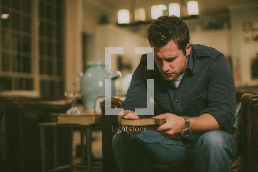 man in prayer looking at the cover of a closed Bible