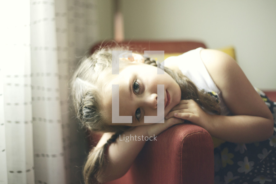 little girl in pig tails with her head leaning on an arm of a chair