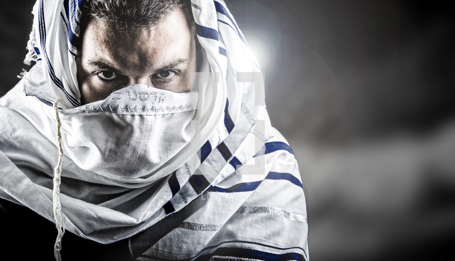 man's face covered by prayer shawl