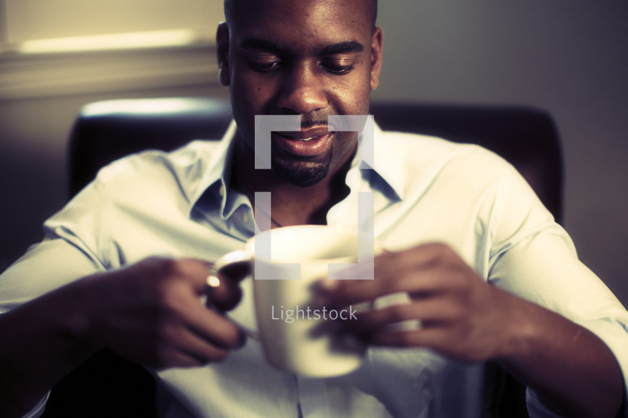 A man sitting down with a cup of coffee
